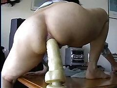 Masked girl rides a toy with her ass tubes