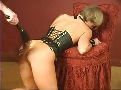 Girl in a leather corset is lightly flogged tubes