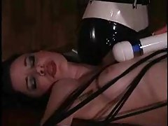 Tied down girl is abused by latex girls tubes