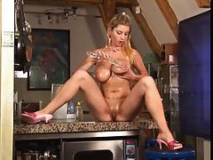 Chick on the kitchen counter showing big tits tubes