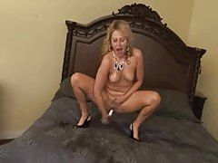 Blonde makes a mess squirting on the bed tubes