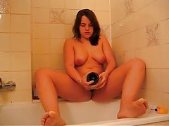 Curvy cutie sits on champagne bottle in bathtub tubes