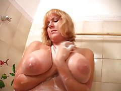 Blonde babe gropes her big natural tits in shower tubes