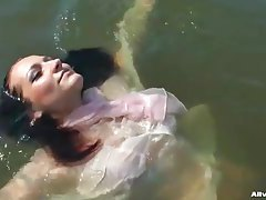 Chick in a sexy blouse takes a dip in the lake tubes