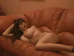She hangs out on the couch and models her big tits tubes