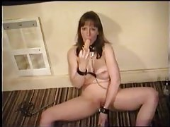 Kinky slut in chains sucks a dildo tubes