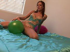 Teen in lingerie rubs body on a balloon tubes