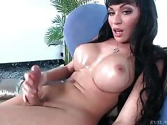 Dark haired tranny with massive tits stroking her massive cock tubes