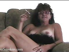 Mature redhead with glasses smoking in her lingerie tubes
