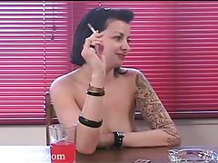 Short haired goth babe with tattoos and piercings enjoying a smoke tubes