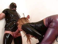 Chained man blown by a beauty in latex tubes