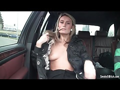 Blonde shows her little tits while smoking in car tubes