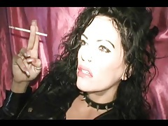 Dark girl in pink lipstick smokes cigarette tubes
