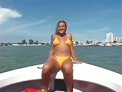 Blonde in yellow bikini models her pussy on a boat tubes