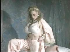 Elegant blonde strips and models her big fake tits tubes