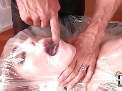 Girl wrapped in plastic and strapped to table tubes