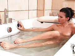 Beauty rubs her feet and legs in bathtub tubes