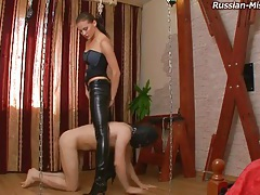 Girl in leather boots and pants tramples him tubes