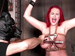 Busty redhead enjoys the tit torture and flogging tubes