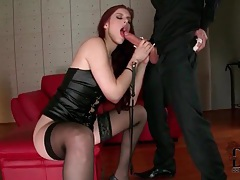 Redhead wears leather and stockings as she sucks tubes