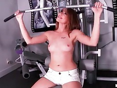 Sporty babe in lipstick strips in gym tubes