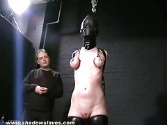 Hooded girl takes painful tit torture tubes