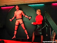 Man on the wheel of pain for leather skirt mistress tubes