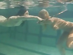 Underwater girls play with a hula hoop tubes