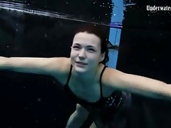 Beautiful girl swims and smiles underwater tubes