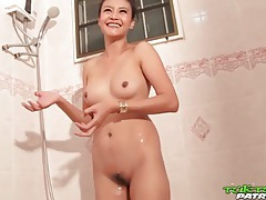 Beautiful young asian washes her body in shower tubes