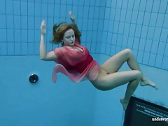 Pretty red dress on girl swimming in the pool tubes