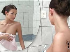 Slim babe pleasures pussy in bathroom tubes
