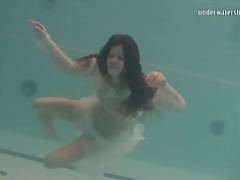 Young brunette swims in sheer white clothes tubes