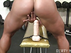 Female bodybuilder fucks a dildo in the gym tubes