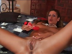 Oiled up beauty fucks a big red dildo tubes