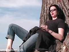 Mina smokes outdoors in a sexy grey sweater tubes