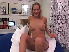 Blonde sits in soft bed and toys her pussy tubes