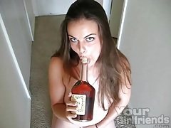 Brunette sucks on a bottle of hennessy tubes