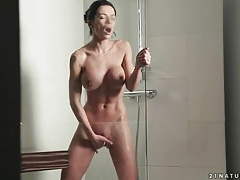 Brunette masturbates in the shower tubes