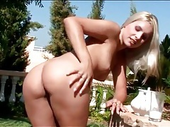 Blonde pours heavy cream on her body outdoors tubes