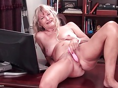 Naked granny on a desk masturbates her cunt tubes
