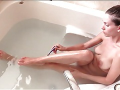Pretty girl shaves her legs in the bathtub tubes