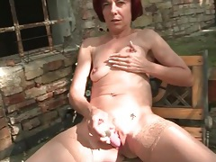 Mature redhead sits outdoors and toys her cunt tubes