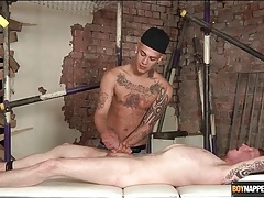 Tattooed guy tied to a table gets a handjob tubes