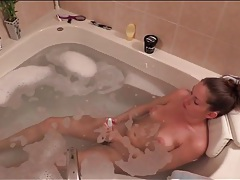 Bathing beauty masturbates with two toys tubes