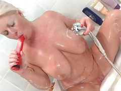 Chubby babe toys her mature pussy in the bathtub tubes