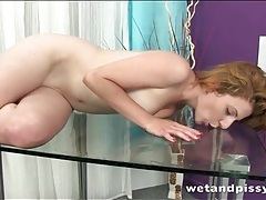 Butt plug babe pisses on a glass desk tubes