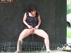 Girl in a dress finds a place to pee outdoors tubes