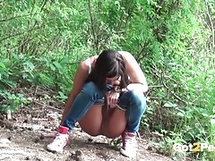 Cute girl on a hike pees by the river tubes