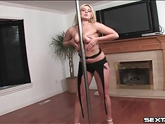 Flexible blonde works the stripper pole with skill tubes